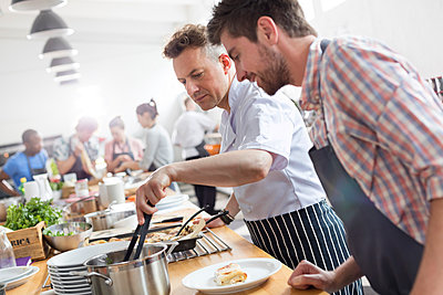 Student watching chef teacher in cooking class kitchen - p1023m1183186 by Agnieszka Olek