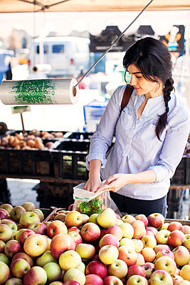 Woman shopping apples at market stall - p1166m995201f by Cavan Images