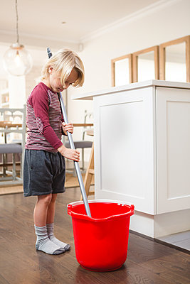 Boy holding floor mop with bucket at home - p1315m1566383 by Wavebreak
