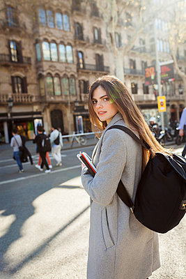 Spain, Barcelona, portrait of young woman with backpack standing at  street - p300m1587806 von Valentina Barreto