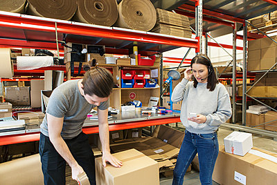Woman using mobile phone while male coworker packing box in warehouse - p426m1580308 by Kentaroo Tryman