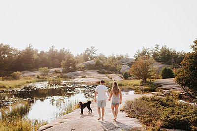 Couple walking with pet dog, Algonquin Park, Canada - p429m2022967 by Sara Monika