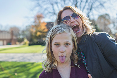 Caucasian mother and daughter making faces outdoors - p555m1305762 by Eric Raptosh Photography