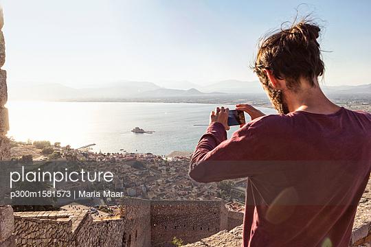 Greece, Peloponnese, Argolis, Nauplia, Argolic Gulf, man photographing view to Bourtzi Castle - p300m1581573 von Maria Maar