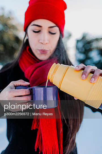 Close-up of woman pouring coffee in mug while standing outdoors during winter - p300m2256972 by Manu Reyes