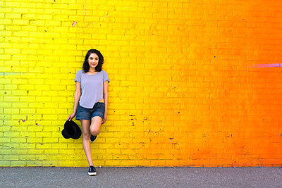 Portrait of smiling young woman leaning against yellow brick wall - p300m1188353 by Giorgio Fochesato