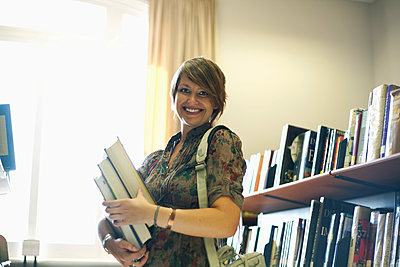 Smiling young woman holding books in library - p300m2250378 by LOUIS CHRISTIAN