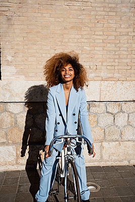 Spain, Valencian Community, Valencia.Lifestyle portraits of afro-haired woman with bicycle and skateboard - p300m2267966 von Rafa Cortés