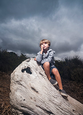 Young boy sitting on tree stump against stormy sky - p429m1014343 by ©JFCreatives