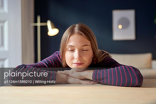 Junge Frau entspannt sich in ihrer Wohnung - p1124m1589210 von Willing-Holtz