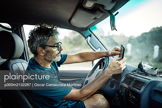 Mature man sitting sitting in his off-road vehicle checking his smartphone - p300m2132287 by Oscar Carrascosa Martinez