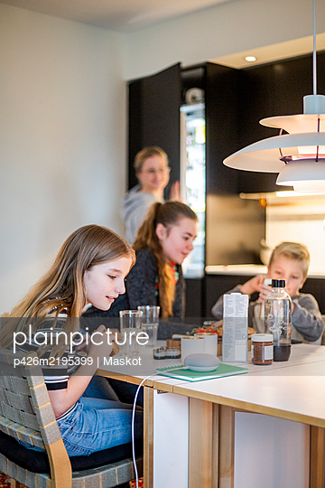 Girl talking to smart speaker while sitting with family at table in modern home - p426m2195399 by Maskot