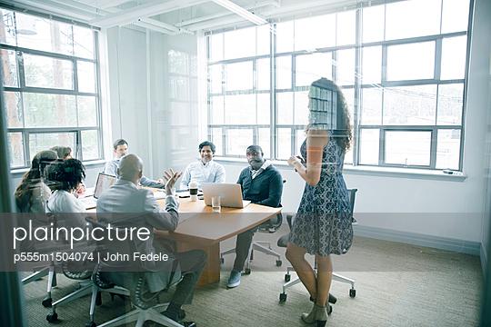 Businesswoman talking behind window in meeting - p555m1504074 by John Fedele
