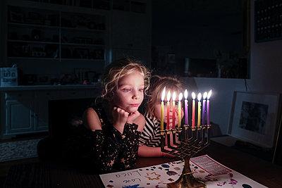 two sisters standing together looking at Hanukkah Menorah fully lit - p1166m2113213 by Cavan Images