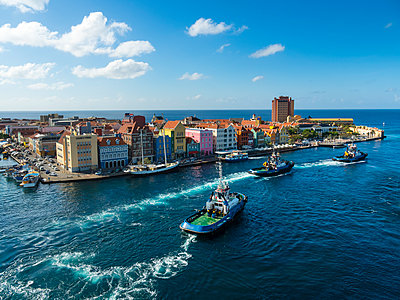 Curacao, Willemstad, Punda, tugboats and colorful houses at waterfront promenade - p300m1228418 by Martin Moxter