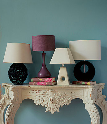 Ornate painted console table with collection of table lamps - p349m695182 by Emma Lee