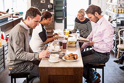 Businessmen and businesswomen having breakfast together in office restaurant - p426m811569f by Maskot
