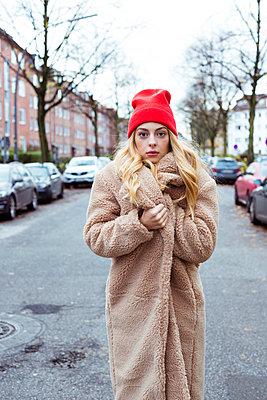 Junge Frau steht im Wintermantel auf der Straße - p432m1502400 von mia takahara