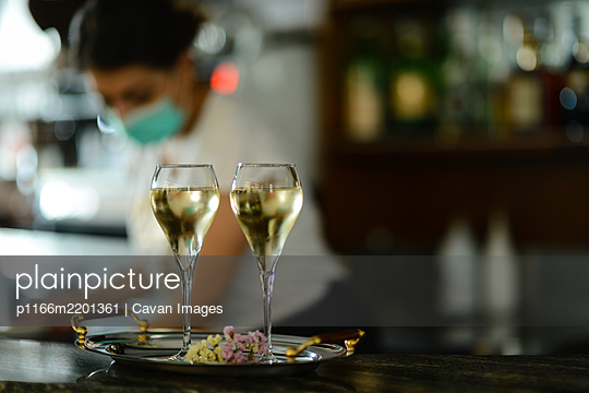 Female bartender wearing face mask prepare sparkling white wine - p1166m2201361 by Cavan Images