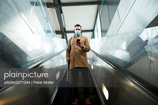 UK, London, Man on escalator - p924m2271244 by Peter Muller
