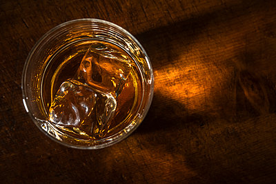 Glass of whiskey with ice cube - p1427m2169142 by Tetra Images