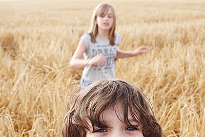 Two kids in a field - p1430m1503584 by Charlotte Bresson