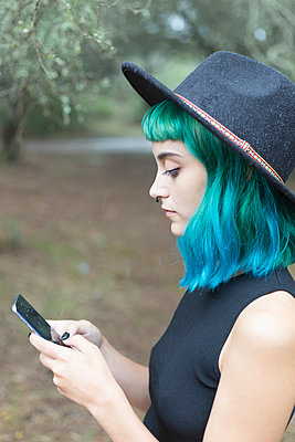 Profile of young woman with dyed blue and green hair using smartphone on rainy day - p300m2120810 by Sus Pons