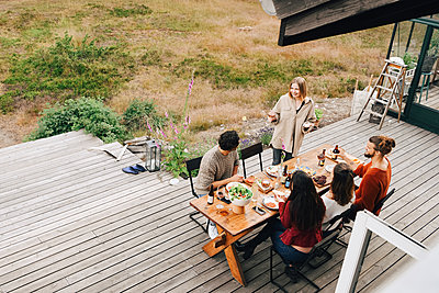 High angle view of woman talking with friends while enjoying dinner in patio - p426m2149266 by Maskot