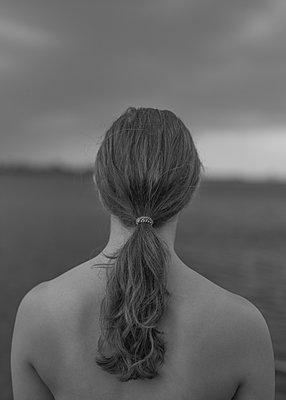 Rückansicht einer jungen Frau mit Pferdeschwanz im Freien - p552m2126288 von Leander Hopf