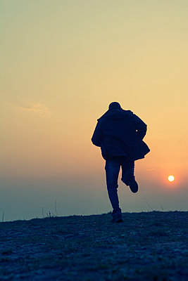 Rear view silhouette of a man running away at sunset  - p794m2073042 by Mohamad Itani