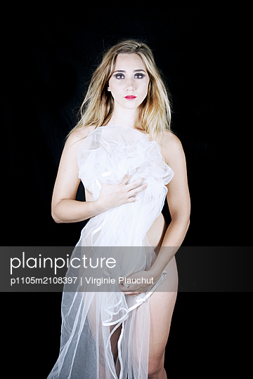Young woman hiding body behind white fabric - p1105m2108397 by Virginie Plauchut
