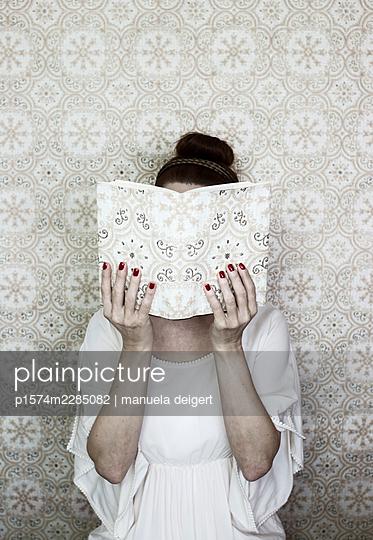 Woman reading a book - p1574m2285082 by manuela deigert