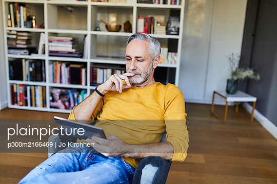 Relaxed mature man at home using tablet - p300m2166469 von Jo Kirchherr