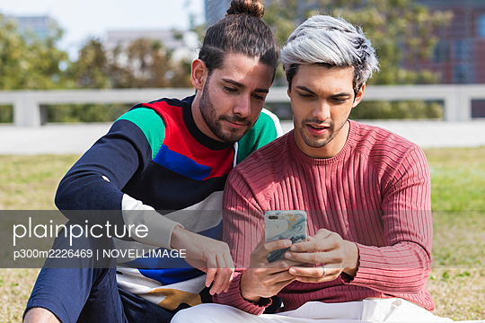 Man with gay partner using mobile phone in park - p300m2226469 by NOVELLIMAGE