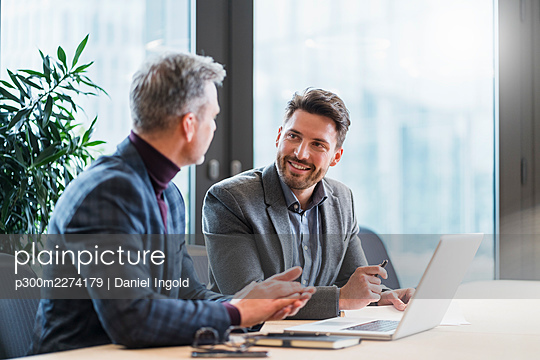 Business people with laptop talking in meeting at work place - p300m2274179 by Daniel Ingold