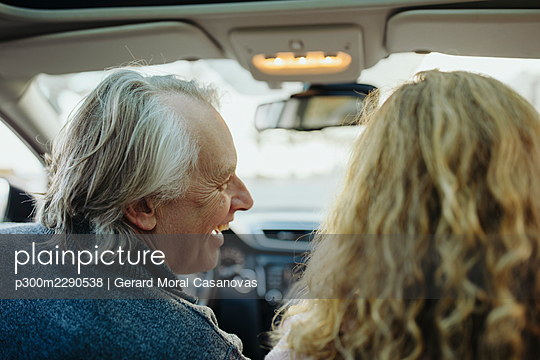 Happy mature man looking at woman while sitting in car - p300m2290538 by Gerard Moral Casanovas