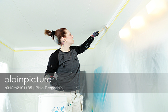 Woman painting ceiling - p312m2191135 by Phia Bergdahl