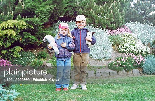 Deutschland, Geschwister mit Kuscheltieren im Garten in der DDR - p986m2223993 von Friedrich Kayser