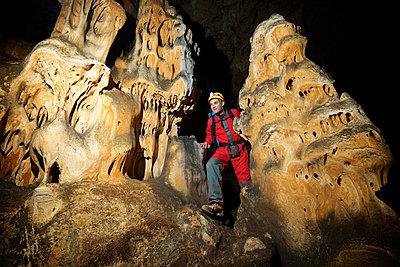 Man hiking in cave - p1166m1532299 by Cavan Social