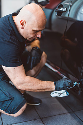 Male worker cleaning car with towel while crouching in workshop - p1166m2060381 by Cavan Images