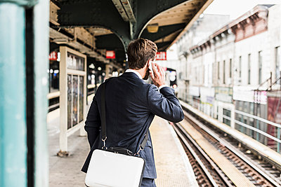 Young businessman waiting at metro station platform, using smart phone - p300m1191676 by Uwe Umstätter