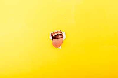 Close-up of boy sticking out tongue through torn yellow paper - p300m2198515 by Josep Rovirosa