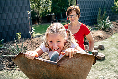 Happy granddaughter playing with grandmother in backyard - p300m2276991 by Oxana Guryanova