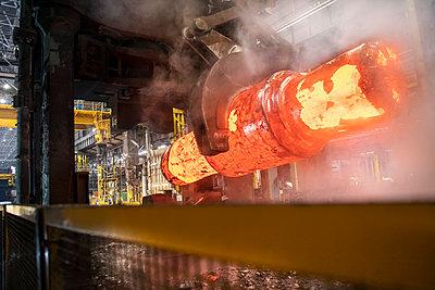 Red hot steel ingot in steel press in steelworks - p429m2146145 by Monty Rakusen