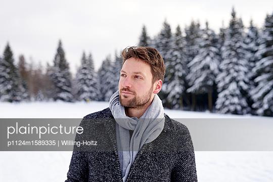 Junger Mann macht einen Winterspaziergang - p1124m1589335 von Willing-Holtz