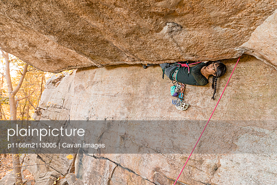 Woman climbing in the fall in the Gunks - p1166m2113005 by Cavan Images