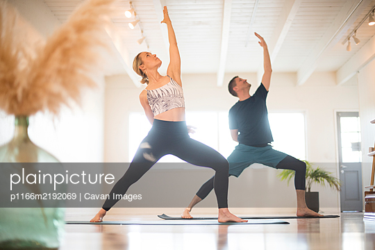 A couple in Reverse Warrior pose during yoga. - p1166m2192069 by Cavan Images