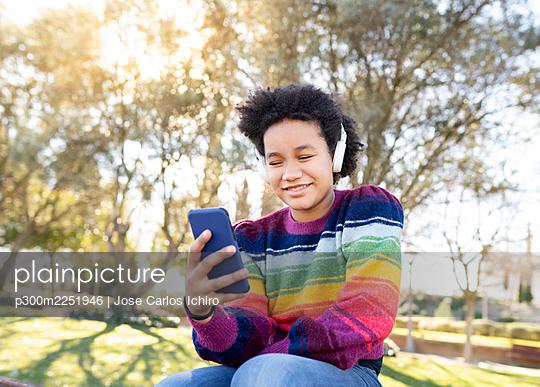 Smiling girl wearing headphones using mobile phone while sitting at park - p300m2251946 by Jose Carlos Ichiro
