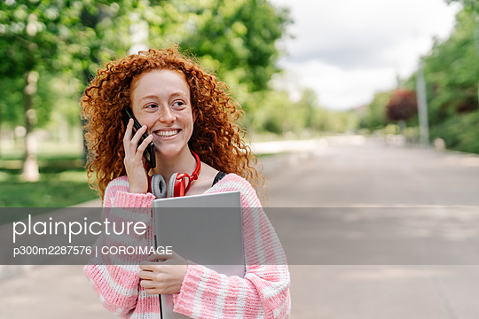 Happy redhead woman with curly talking on smart phone at park while looking away - p300m2287576 by COROIMAGE