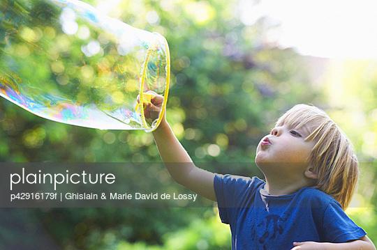 Boy blowing oversized bubble in backyard - p42916179f by Ghislain & Marie David de Lossy